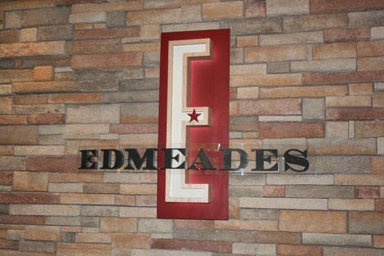 Carved maple E is back lit using a halo effect, and mounted on a rusty red metal panel.  The lettering is 3/4"