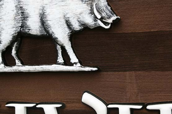 Hand carved pig on a stained sandblasted cedar background.  The pig was painted to match the