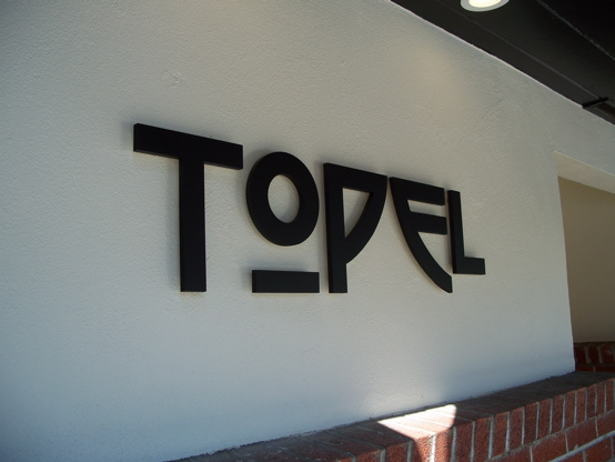 "1/2"" aluminum letters painted matte black and pin-mounted approx. 1/2"" off stucco surface"
