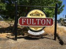 This sign identifying the Town of Fulton is 3 dimensionally carved urethane over resined MDO with palladium leaf and acrylic house paints... with custom powdercoated posts and bracket.
